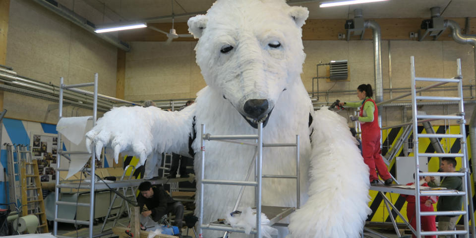 Picture of people working on a polar bear sculpture.